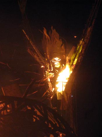 A sculpture by Aragorn bursts into flame after the 'Message in a Bottle' performance washed ashore hundreds of glowing plastic bottles onto his beach in Trellis Bay