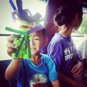 The youngest member of the Stratton ABC Foundation in Thailand holds up his new toy Samurai that he made from re-purposed plastic that would have been otherwise sent to the land fill.